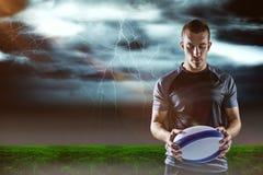 Image composée du joueur sérieux de rugby tenant la boule Image stock