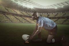 Image composée du joueur sûr de rugby semblant parti tout en gardant la boule sur donner un coup de pied la pièce en t avec 3d Photographie stock libre de droits
