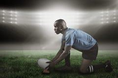 Image composée du joueur sûr de rugby semblant parti tout en gardant la boule sur donner un coup de pied la pièce en t 3d Photos libres de droits