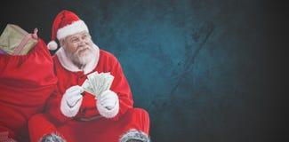 Image composée du père noël se reposant par le sac complètement de cadeaux comptant des notes de devise Photos stock