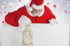 Image composée du père noël tenant la lanterne de Noël sur le conseil blanc Photos stock