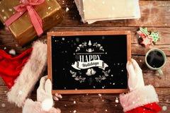 Image composée du père noël tenant une ardoise avec le texte de Joyeux Noël photographie stock libre de droits