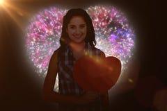 Image composée du portrait de la femme de sourire tenant la carte de coeur Image stock
