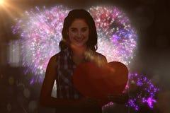 Image composée du portrait de la femme de sourire tenant la carte de coeur Images stock