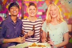 Image composée du portrait de trois amis féminins ayant la bouteille de bière et de pizza dans la partie Image stock
