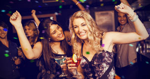 Image composée du portrait des amis ayant une boisson et une danse Photographie stock libre de droits