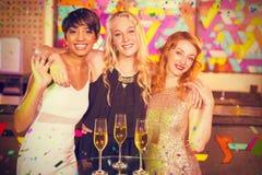 Image composée du portrait des amis féminins de sourire se tenant avec le bras autour dans la barre Image stock