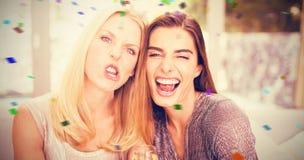 Image composée du portrait des amis féminins faisant les visages drôles Images stock