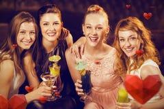 Image composée du portrait des amis féminins tenant des verres de cocktail dans la barre Photos stock