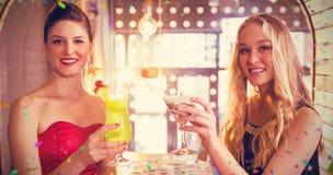 Image composée du portrait des amis féminins tenant le verre du cocktail dans la barre Photo stock