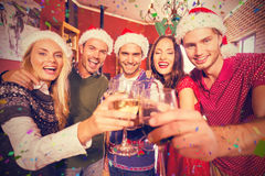Image composée du portrait des amis portant le grillage de chapeaux de Noël Image stock