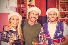 Image composée du portrait des amis utilisant des chapeaux de Noël Photographie stock libre de droits