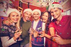 Image composée du portrait des amis utilisant des chapeaux de Noël avec la cannelure de champagne Images stock