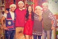 Image composée du portrait des amis utilisant des chapeaux de Noël se tenant ensemble Images stock