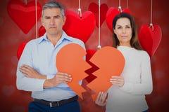 Image composée du portrait des couples tenant le papier 3d de forme du coeur brisé Image stock