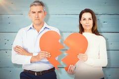 Image composée du portrait des couples tenant le papier de forme du coeur brisé Photos stock