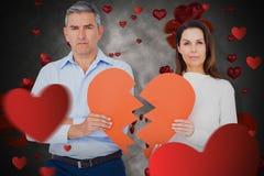 Image composée du portrait des couples tenant le papier de forme du coeur brisé Photo libre de droits