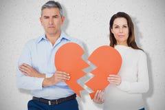 Image composée du portrait des couples tenant le papier de forme du coeur brisé Images stock