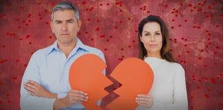 Image composée du portrait des couples tenant le papier de forme du coeur brisé Image stock