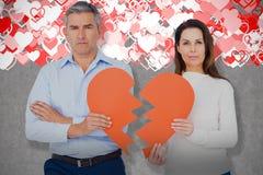 Image composée du portrait des couples tenant le papier de forme du coeur brisé Photographie stock libre de droits