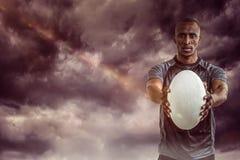 Image composée du portrait du sportif montrant la boule de rugby Images libres de droits