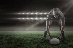 Image composée du portrait du sportif tenant la boule tout en jouant le rugby 3d Photographie stock libre de droits