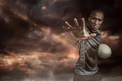 Image composée du portrait en gros plan du sportif faisant des gestes tout en se tenant avec la boule de rugby Image stock