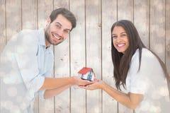 Image composée de jeunes couples attrayants tenant une maison modèle Photos stock