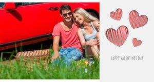 Image composée des couples de sourire se reposant sur l'herbe ayant le pique-nique ensemble Images stock