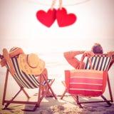 Image composée des couples détendant sur la plage Photographie stock libre de droits