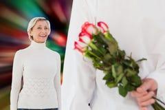 Image composée du bouquet de dissimulation de l'homme des roses d'une femme plus âgée Photographie stock