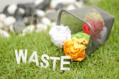 Image concept, crumple color paper on metal bin, green grass and Royalty Free Stock Photography