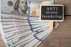 Image conceptuelle avec le tableau noir avec le texte et le x22 ; anti laundering& x22 d'argent ; et cent billets d'un dollar image stock