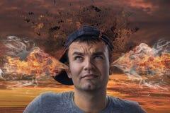 Image conceptuelle d'un jeune homme tendu avec de la fumée sortant de h images stock