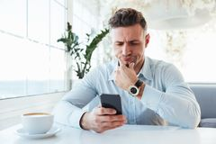 Image of confident businesslike man sitting alone in city cafe w. Ith cup of cappuccino and browsing internet in black smartphone Royalty Free Stock Images