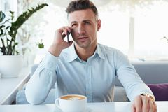 Image of confident businesslike man sitting alone in city cafe w. Ith cup of cappuccino and talking on black smartphone Royalty Free Stock Photos