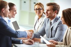 Agreement. Image of confident businessmen handshaking at meeting Stock Photos