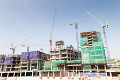 Image of construction site against blue sky with multiple tower cranes Royalty Free Stock Photos