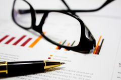 Business charts with glasses and pen. Image containing Business charts with glasses and pen illustrating business analysis and financial review stock image