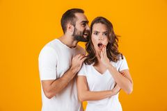 Image of content man whispering secret or interesting gossip to woman in her ear, isolated over yellow background. Image of content men whispering secret or royalty free stock image