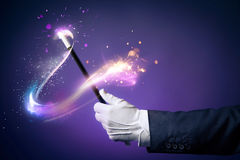 Image contrastée de main de magicien avec la baguette magique magique Image stock