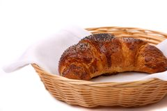 Image of croissant with poppy in a basket. Stock Image
