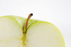 An image of a cross-section of a green apple with stem Royalty Free Stock Photography