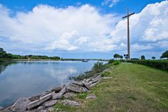A cross sits along the waterside surrounded by green grass with white fluffy clouds in the sky. This is an image of a cross sitting on the banks of a peaceful Stock Image