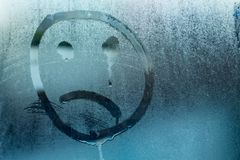 Image of a crying face on a glass stock photos