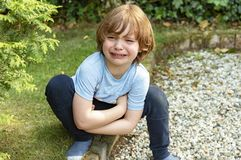 Image of a crying little boy who has crawled angrily in a corner of the garden. Image of an angry crying boy with brown hair, blue t-shirt and dark long pants royalty free stock images