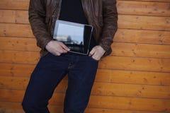 Image cultivée avec le jeune homme élégant tenant le comprimé numérique avec un écran vide Image stock