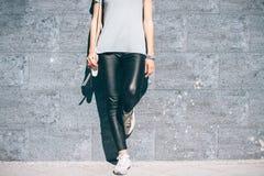 Image cultivée d'une femme dans le pantalon noir et un T-shirt bleu Photo stock
