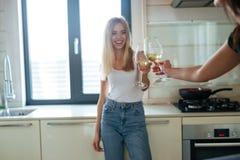 Image cultivée de deux femmes faisant tinter des verres à vin Photo stock