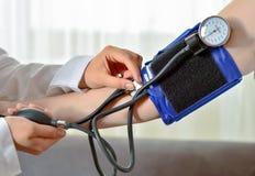 Image cultivée de docteur féminin vérifiant la tension artérielle du patient à la table Images stock